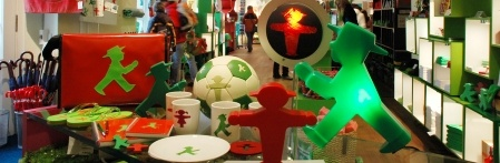 Ampelmann store (ampelmann.de).  Has ampelmann on table lamps, sweets, ice cube trays, kitchen sponges, bags, cutlery and notepads.     5 locations.  Closest is on corner of Unter den Linden & Friedrichstrasse near the Brandenburg Gate.  Others are in Potsdamer Platz and Hackescher Markt.      Mon.-Fri. from 9:00-18:00 clock opening times: Mon - Sat 09:30 to 22:00 Sun 10:00 - 19:00   Note: open Sundays.
