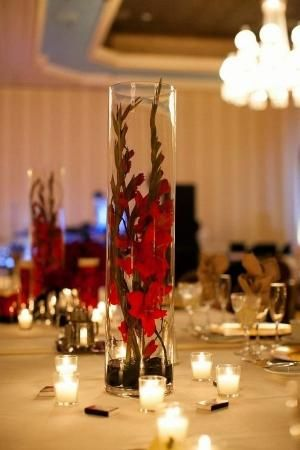 Place 2 stems of the same color gladiola stems in a tall cylinder vase to create a dramatic and budget friendly centerpiece for a wedding or other special event.  Be sure to give the gladiolas time to open. #wedding #gladiola redcenterpiece by lizzie
