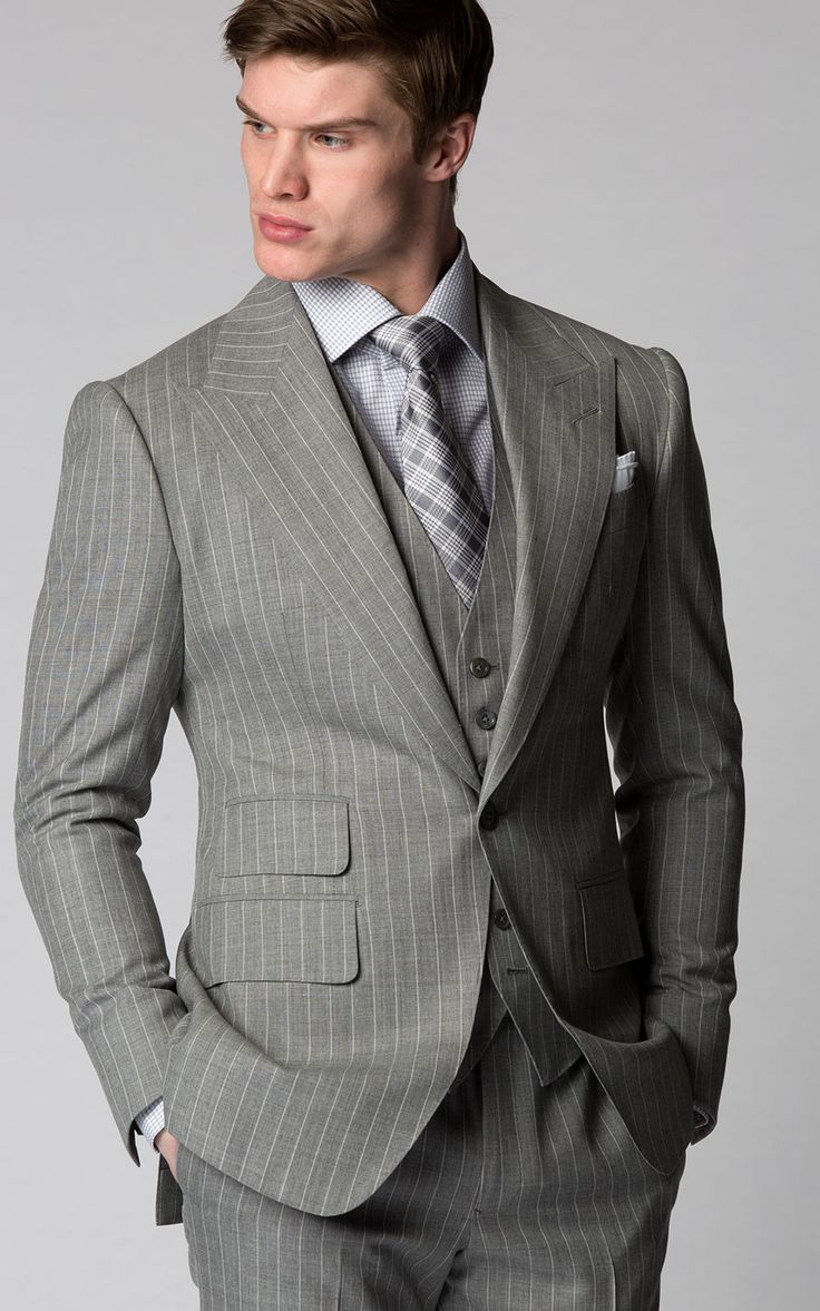 Custom Bespoke Light Grey Pinstripe 3-Piece Summer Suit with Peak Lapels from Michael Andrews Bespoke. Stuck in the office this summer? Assure you'll be a standout in this 1-button light grey pinstripe suit which features a peak lapel and ticket pocket. This dashing piece is woven from a cool wool plain weave from Holland & Sherry.