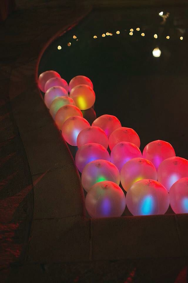 Night pool party with glow stix in balloons