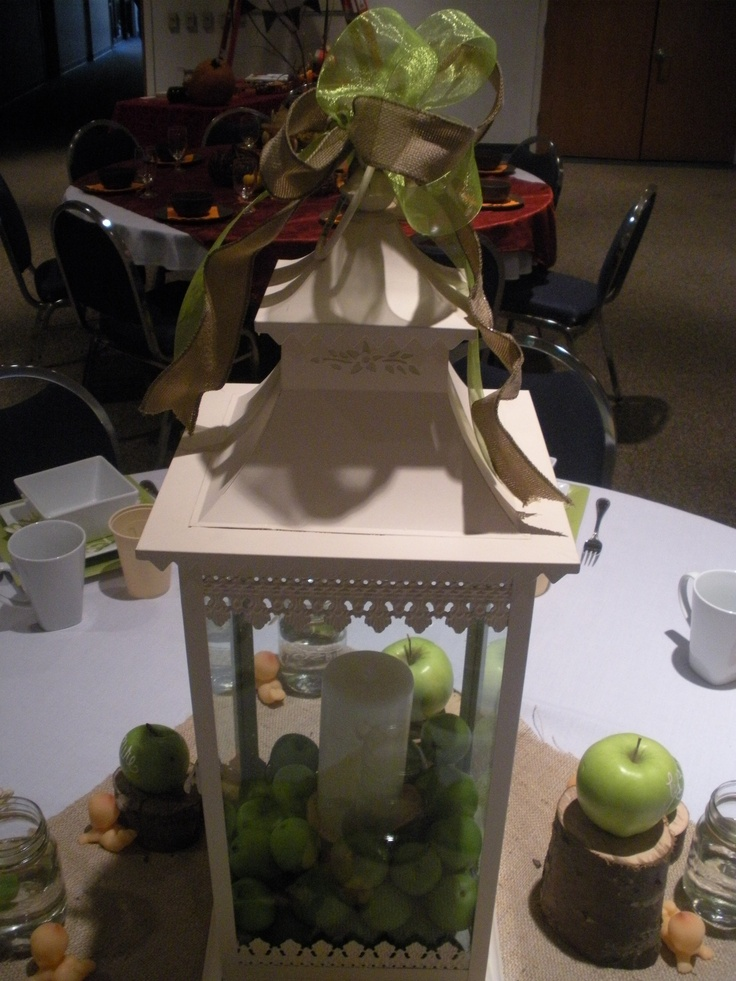 Lantern centerpiece filled with small green apples baby