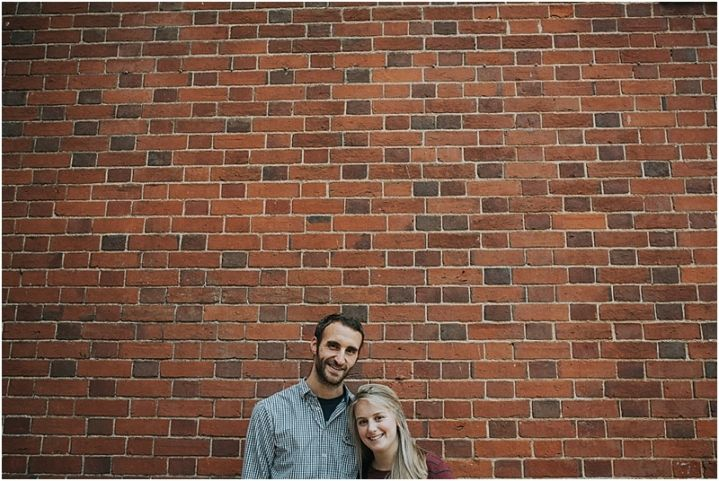 Autumn New Forest engagement shoot couple hugging by large brick wall