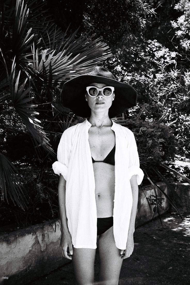 Black wide brimmed hat, white sunglasses, and white unbuttoned oxford layered over a black string bikini