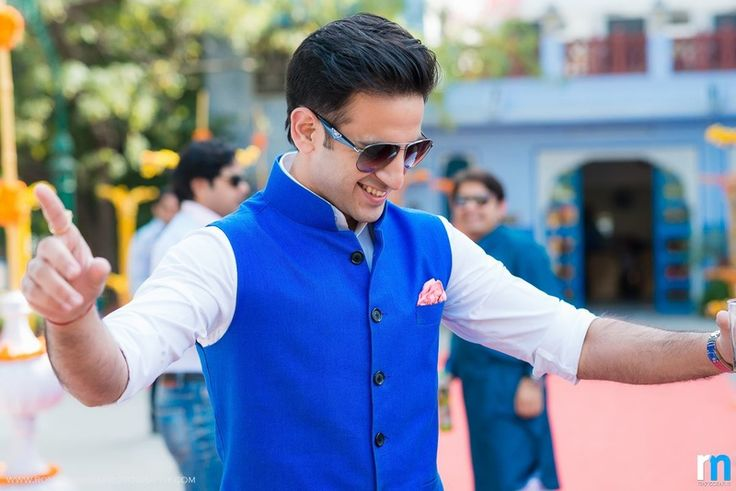 Groom pulling it off in a cobalt blue nehru jacket styled with white kurta and churidar. Groom wear done right!