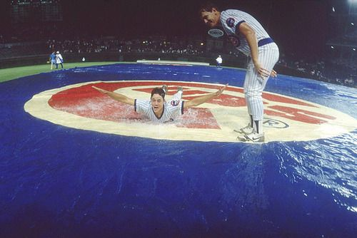 Cubs pitcher Greg Maddux slides on a wet infield tarp during a rain delay in the first night game at Wrigley Field on Aug. 8, 1988.  Maddux was voted into the Hall of Fame with 97.2 percent of the vote.  (Heinz Kluetmeier/SI)
