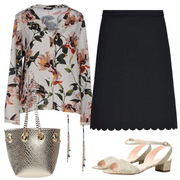 La casacca ha grandi fiori stampati, ben si abbina alla gonna al ginocchio, nera col bordo smerlato i sandali gold e dal tacco comodo, la borsina a secchiello e gli orecchini colorati.