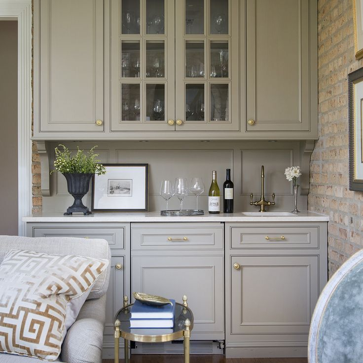 Amazing Living Room Features A Wet Bar Boasting Gray Cabinets Adornedwith Brass Hardware Topped With Natural Stone Fitted Square Sink And Gold