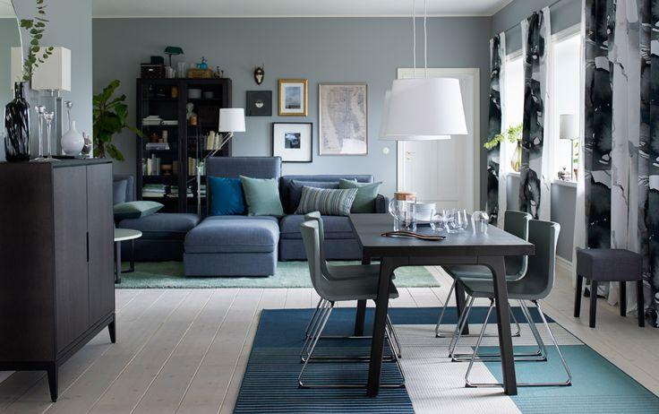Coin repas dans un salon bleu avec table en bois brun foncé et 4 chaises en cuir vert.