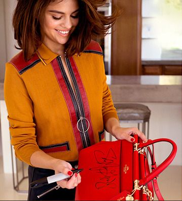"""June 15: Selena signing her red """"Selena Grace"""" handbag for the """"Coach x Selena Gomez"""" competition. Enter to win here: http://www.coach.com/selenasweeps"""
