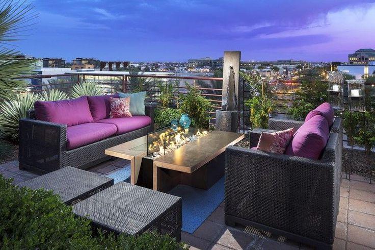 aménager une terrasse d'appartement avec des meubles en résine tressée, coussins mauves et foyer extérieur