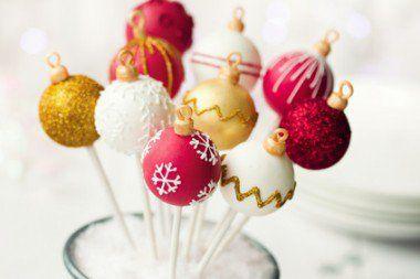 Cake Pops de Natal:Massa 2 xícaras (chá) de farinha de trigo 1 xícara (chá) de açúcar 1 xícara (chá) de chocolate em pó 1 xícara (chá) de leite 6 ovos 1 colher (sopa) de fermento em pó Glacê real Chocolate branco fracionado derretido Corante em gel nas cores desejada Glitter em gel comestível Palitos para pirulitos