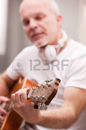 seniors musique: homme d'âge mûr jouer de la guitare à la maison sur un tapis dans son salon