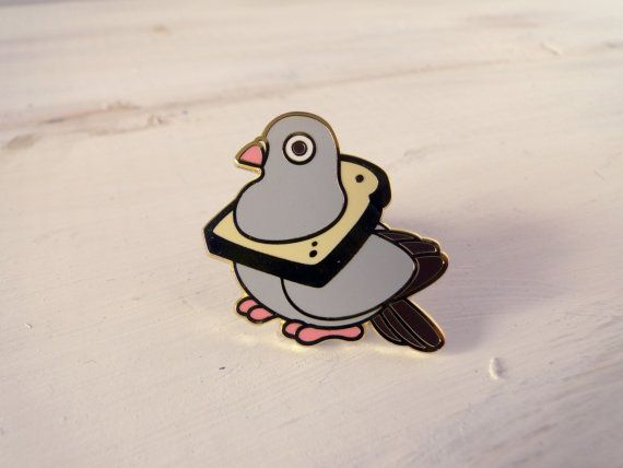 This stylish pigeon.   Pin is polished, gold-plated hard enamel, with a rubber clutch backing. Measures approximately 2.5 cm wide. This is a Red Ribbon Shoppe original design.
