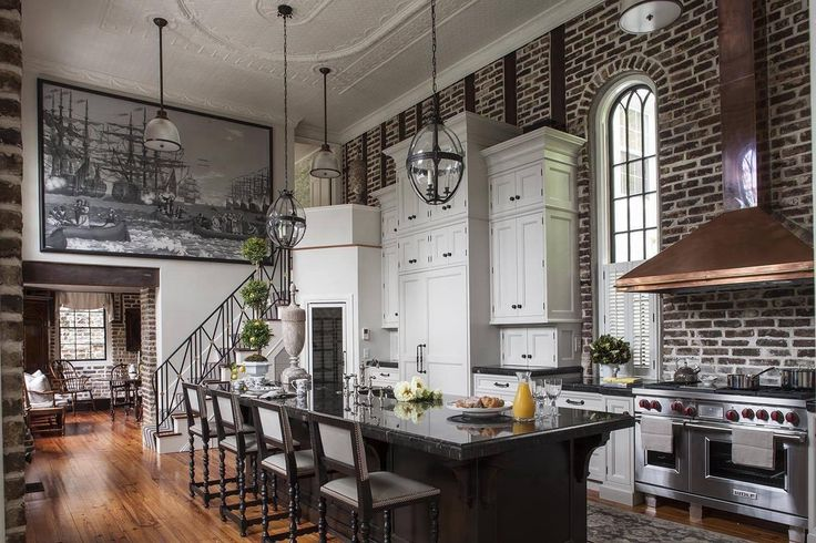 Kitchen with elevated ceilings, exposed brick wall and a metallic stove with copper hood in a pre-Civil War home - Charleston, SC