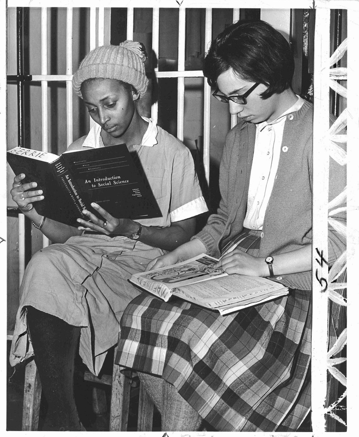 Original vintage press photo showing two students studying while incarcerated at the Baltimore City jail in 1964.  The students had been protesting segregation at a local theater and were arrested.