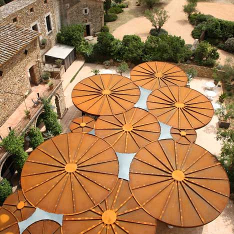 Dutch architects Concrete designed flattened parasols of rusted steel to shelter the terraced restaurant outside a historic castle in Girona, Spain. The canopy is composed of twelve steel-coated discs that overlap one another to cover up to 200 diners at the restaurant. Gaps between circles on the canopy surface are filled with glass. Transparent curtains