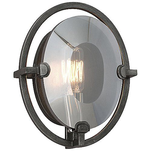 """The Prism Oval Wall Sconce by Troy Lighting gives an elegant perspective on transitional lighting, showcasing a Crystal lens that sits in front of a vintage Edison bulb. The design is anchored by a Hand-Worked Wrought Iron frame (finished in Graphite) which contrasts beautifully with the refined appearance of the lens. 9""""Hx7""""Wx4""""D.  1x60W"""