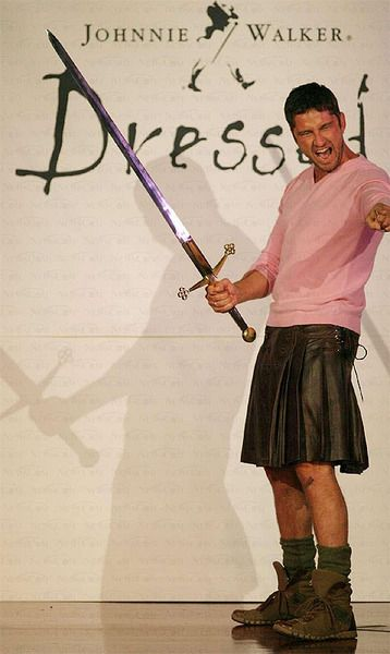 Gerard Butler with a sword....in a pink shirt....and a leather kilt!  ahhhhhh