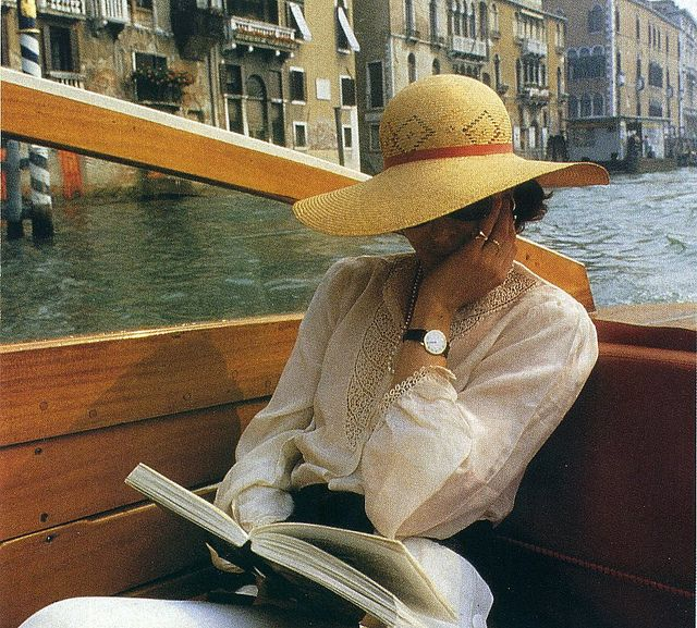 read a book on a bout in Venice wearing a big sun hat and a white dress...