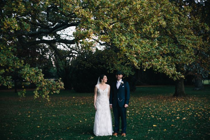 Sophia and Dylan stand under the autumn trees in the gardens of Bendooley Estate wedding venue, Berrima, Southern Highland, Australia.