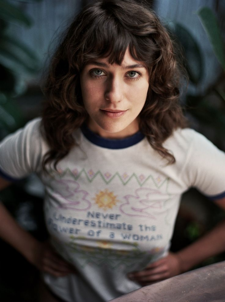 """Wearing a shirt that reads: """"never underestimate the power of a woman"""", Lola Kirke poses for So It Goes Magazine"""
