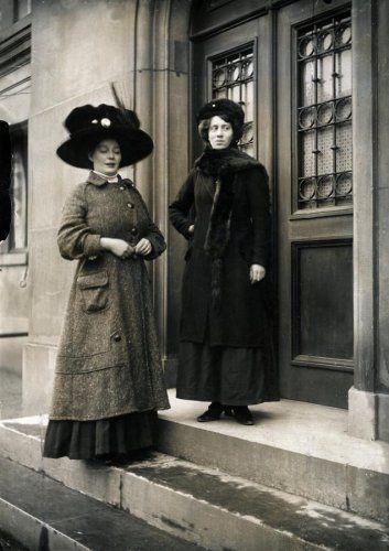 Dameskleding vòòr 1914. Twee vrouwen in herfst-winterkleding, de linkervrouw in een lange jas van visgraattweed met een grote hoed met veer, de rechtervrouw in een jas met bontsjaal en bonthoed. Plaats onbekend, 1910.