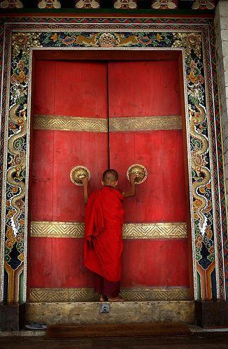 BHUTAN:THE LAST SHANGRI LA | A Buddhist monk enters the formidable doors of Trongsa Dzong, Bumthang District, Bhutan √