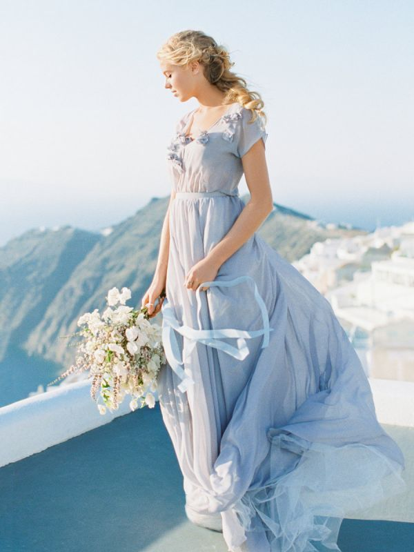 Made out of sky-blue silk chiffon, this airy gown features a V neck, sheer cap sleeves, and a sprinkling of delicate silk flowers.