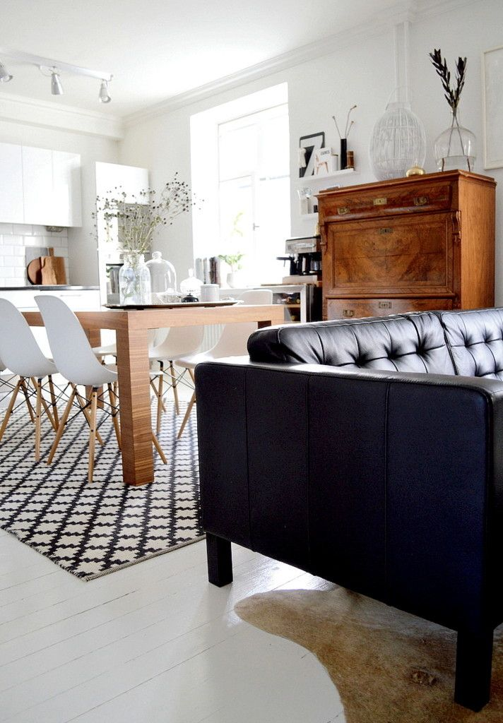 White kitchen, Eames DSR chairs, a black leather couch and a cowhide plus some wooden elements.