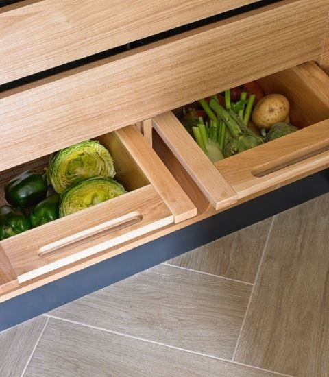 Light wood interior of pantry cupboard for Esher blue-grey kitchen with built-in vegetable storage drawers.