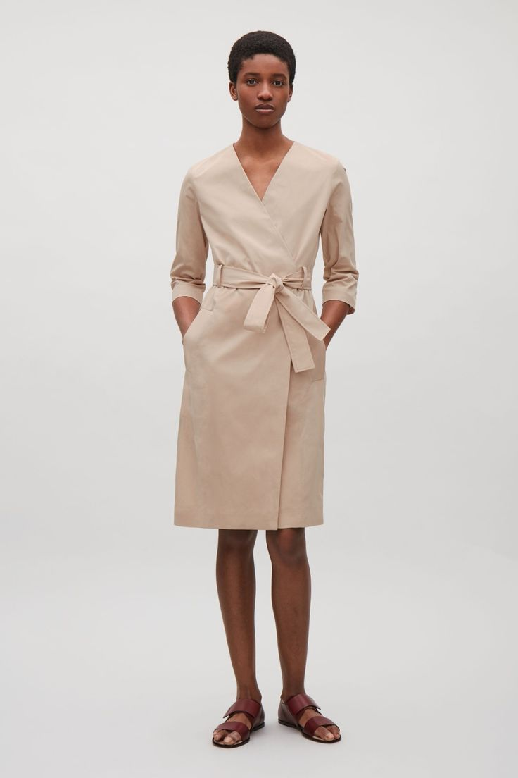 Designed with classic trench coat details, this dress is made from a cotton blend with a twill finish. A wrap-over front, it has a simple v-neckline, large welt pockets and a wide belt loops with a detachable fabric belt.