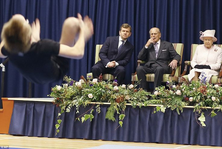 Taking a tumble: The Duke of Edinburgh looks impressed as he watches a young gymnast in ac...