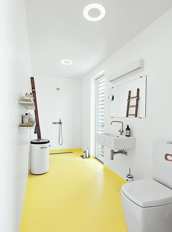 In the bathroom of this tiny floating home in Denmark, the epoxy floor transitions from whitish gray to submarine yellow. The black-and-white industrial laundry bin is by Vipp. Modern bathroom with yellow floors