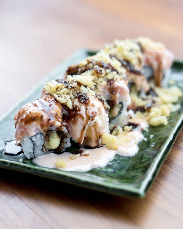 """Superstar Roll."" Filling of crispy mozzarella cheese, marinated cod and pollock roe; slices of fatty tuna on top. Drizzled with black ponzu and house ""oko"" sauce, sprinkled with seasoned tempura flakes."