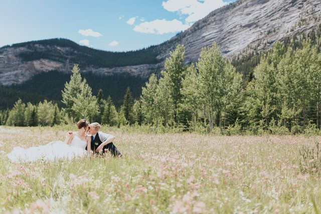 bride & groom snuggling in a field in Nordegg surrounded by mountains