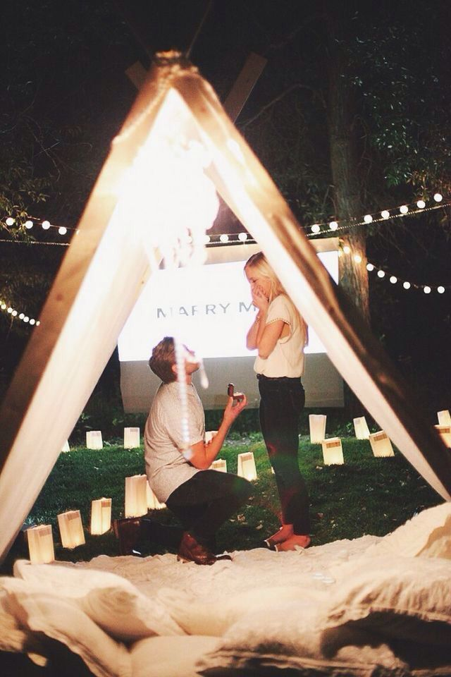 romantic wedding proposal with movie, tent, and candles