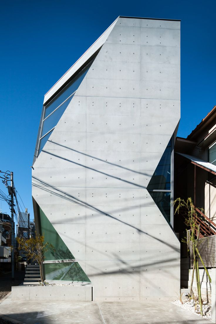 """R · torso · C house in Tokyo by Atelier Tekuto.  Volcanic ash is mixed into the concrete shell of this angular house in central Tokyo, which was designed by Atelier Tekuto for a pair of chemists.  The ash increases the strength and durability of the concrete, as well as helping to provide humidity control, said the architects. The corners of the house were """"pruned"""" away to create windows with views of the sky and street from the narrow urban plot."""