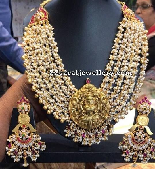 Small round shaped Basara pearls bunches embellished multi layers heavy necklace with Antique work 22 carat gold Lakshmi pendant attached in the center