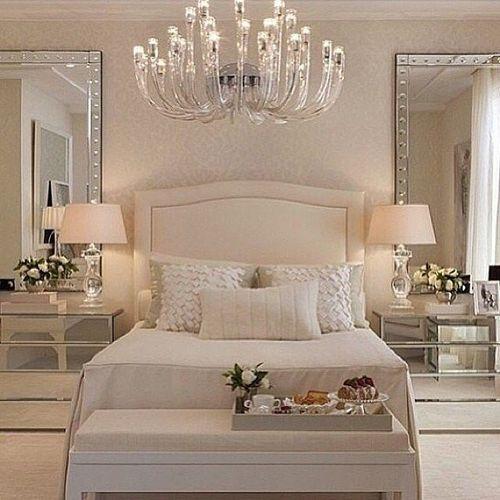 quarto de casal decorado em tons de beje com espelhos grandes nas laterias da cama, ecriados mudos espelhados
