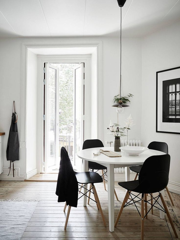 Bright Dining Room With A Round White Table Surrounded By Black Eames  Chairs.