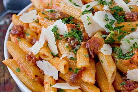 Penne alla Vodka  Ingredients: 2 tablespoons olive oil  3 ounces thinly sliced prosciutto, finely chopped (optional) 1/2 sweet onion, finely chopped 1 tablespoon tomato paste 3-4 garlic cloves, pressed 1 28-ounce can diced tomatoes (I like chef's cut) 1/4 teaspoon red pepper flakes, to taste 2 teaspoons sugar 1 teaspoon kosher salt 1/3 cup vodka 1/2 cup heavy cream 1 pound (16 ounces) penne pasta Parmesan cheese, for serving  Chopped parsley, for serving