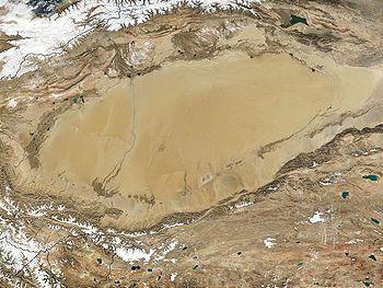 Desierto de Taklamakán, bajo la superficie del cual yace la cuenca sedimentaria del Tarim, una acumulación de varios kilómetros de espesor de sedimentos traídos desde la meseta tibetana (al sur) y de la cordillera del Tian Shan (al norte) por la red fluvial. La longitud de la cuenca es de unos 1000 km; el norte está aproximadamente en la parte superior de la imagen.