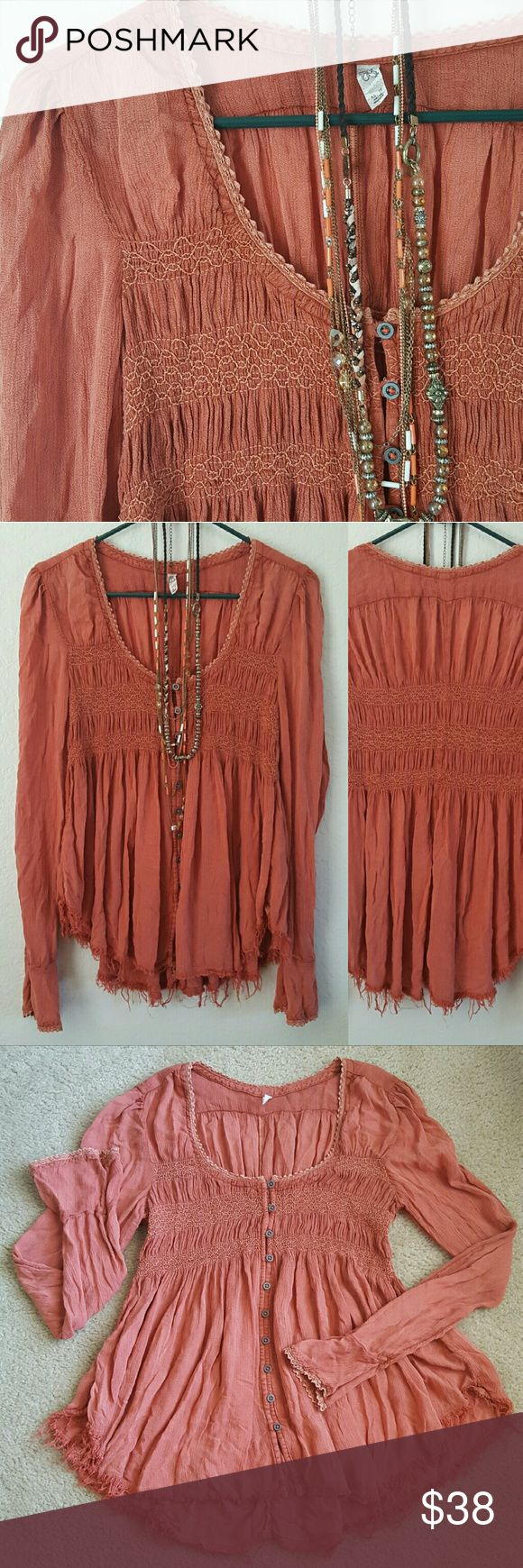 """Free People Blue Bird Smocked top pink sand Gorgeous Free People boho style """"Blue Bird smocked"""" top. Has a worn tattered look to it. Bell sleeves, metal button front, smocking on front and back, fraying at bottom and lace details at neck and sleeves.   No visible signs of wear.   Size xsmall. Underarm to underarm 15"""" length 24-26""""  Some stretch in smocking. Buttons gap so would need something underneath. Free People Tops Blouses"""