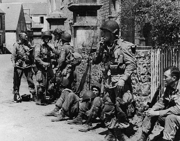 US paratroopers of the 82nd Airborne Division relaxing after liberating the village of Sainte-Mere-Eglise in Normandy, during World War II, 8th June 1944. Pin by Paolo Marzioli