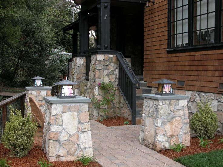 Stone pillars with Arroyo lighting fixtures surround front entry seating area.