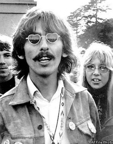 """George Harrison, wearing heart-shaped sunglasses, with wife Patti Boyd Harrison at his side, tours the Haight-Ashbury in San Francisco during the Summer of Love on August 8, 1967. He paused on Hippie Hill in Golden Gate Park and played an acoustic version of """"Here Comes the Sun""""."""