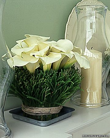 (Lilies and Needles)  Double-sided tape and pine needles transform an ordinary glass vase into an ideal container for crisp white lilies. Use these inventive creations as the center of attention at your winter occasions.