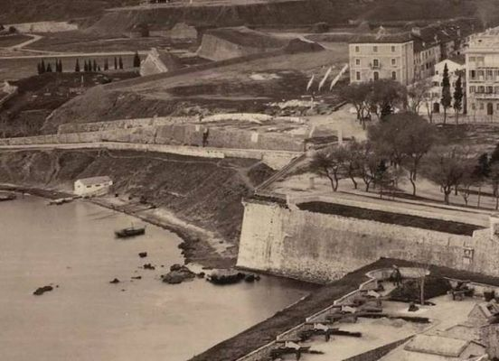 Mερική άποψη της πόλης της Κέρκυρας, από την επάνω πλατεία έως το σημερινό όρμο της Γαρίτσας (λεωφόρος Δημοκρατίας), μέσα από μία φωτογραφία ντοκουμέντο για την ιστορία της Κέρκυρας. Φαίνεται η Ιόνιος Ακαδημία πριν βομβαρδιστεί , την 14η Σεπτεμβρίου 1943, από τους Γερμανούς και πάρει τη σημερινή της όψη.