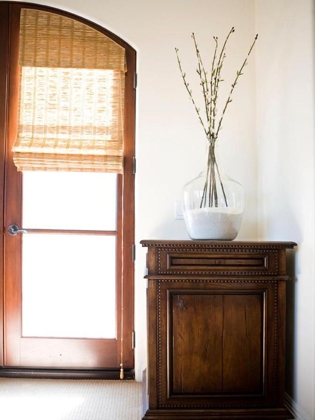 Door-length wooden Roman shades contribute to the simplicity of this entryway