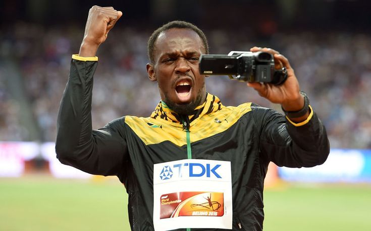 Jamaica's Usain Bolt films himself on a video camera as he waits to receive his gold medal for the Men's 100m at the IAAF World Championships at the Beijing National Stadium
